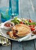 Hearty lamb pie with salad and ketchup
