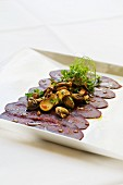 Lightly pickled venison fillet garnished with fried mushrooms and parsley