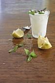 Lemon granita, lemons and fresh mint on a wooden surface