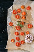 Baked cherry tomatoes with salt and garlic on backing paper