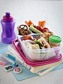 A lunch box with a sandwich, fruit, vegetables and salted pretzels for school