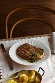 Grilled rib-eye steak with herb sauce and fried potatoes