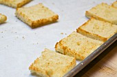 Toasted white bread with the crusts cut off on a baking tray