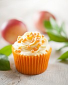 A cupcake with nectarine cream and orange sugar pearls