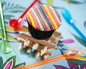 A cupcake decorated with coloured fondant stripes