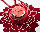 A red velvet cupcake decorated with red fondant flowers