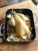 Corn-fed chicken on vegetables in a roasting tin