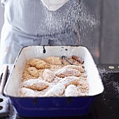 Quark dumplings with buttered crumbs being dusted with icing sugar