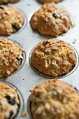 Blueberry and yoghurt muffins with oats in a muffin tin