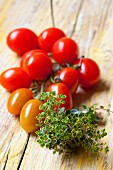 Cherry tomatoes and lemon thyme on a wooden surface