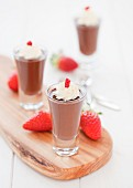 Three small chocolate pots with cream and strawberries