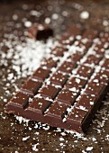 A bar of dark chocolate sprinkled with sea salt flakes
