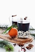 Two glasses of mulled wine with spices and sprigs of fir