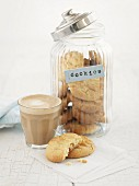 Cookies in a storage jar and caffe latte