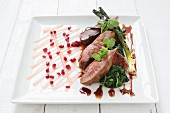 Roasted duck breast with spring onions, spinach and pomegranate seeds