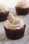 Festive cupcakes decorated with little fondant babies for a baby shower