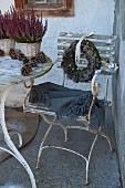 Vintage Gartenstuhl mit abgeblätterter Farbe und grauem Plaid, an Rückenlehne aufgehängter Kranz mit Tannenzapfen