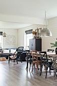 Bugholzstühle um Esstisch unter Pendelleuchte mit Metallschirm, im Hintergrund gemütliche Couchecke in offenem Wohnraum mit weisser Holzverkleidung