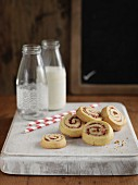 Swiss roll, sliced, and bottles of milk on a wooden board