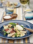 Nudelsalat mit Hähnchen, Wurst, Erbsen und Pinienkernen