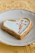 A heart-shaped biscuit with an egg white glaze and a stamped motif