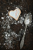 A heart-shaped biscuit, icing sugar and a spoon