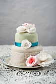 A cake decorated with fondant icing and sugar roses