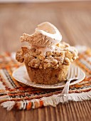 An apple crumble cupcake top with a scoop of ice cream