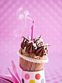 A birthday cupcake with a smoking candle