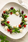 A festive wreath made from basil, rosemary, capers, mozzarella, olives and cherry tomatoes