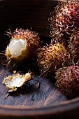 Rambutans in a wooden bowl, cut open