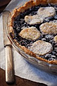 A mulberry pie with icing sugar topped with biscuits