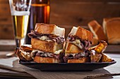 Roast beef and cheese sandwiches with potato wedges and beer