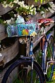 Altes Fahrrad mit Brotzeitkorb an einem Holzzaun