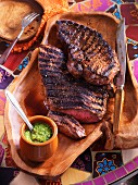 Grilled steak with mint sauce on a laid table (South America)