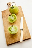 Green tomatoes, whole and halved, on a chopping board with a knife