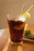 Cola with rum, limes and ice cubes in a ray of sunshine