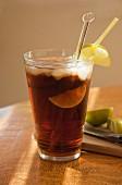Cola mit Rum, Limetten und Eiswürfeln im Sonnenlicht