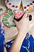 Frau mit angebissenem Pink-Cupcake
