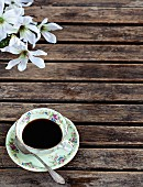A cup of black coffee on an old wooden table
