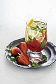 Water flavoured with strawberries, lemon and basil