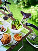 A bicycle picnic with chicken, a dip and salad in a park