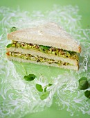 A double-decker sandwich with avocado and bean sprouts