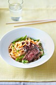 Grilled beef on a bed of rice noodles with mange tout, coriander and chilli flakes