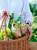 A woman holding a picnic basket with mineral water, grapes and freshly made wraps
