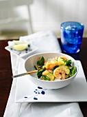 Garnelencurry aus dem Wok mit Spinat, Zucchini und Zwiebeln auf Reis
