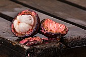 Aufgeschnittene Mangostane auf Holzkiste