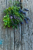 A bunch of fresh herbs with lavender flowers on a wooden surface