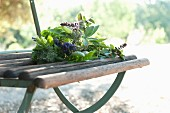 A bunch of fresh herbs with lavender flowers on a garden chair