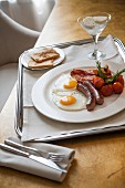 A hearty breakfast featuring fried eggs, sausages, bacon and toast
